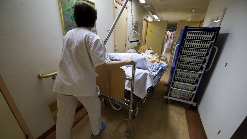 Kvinna inom vården drar sjukhussäng.