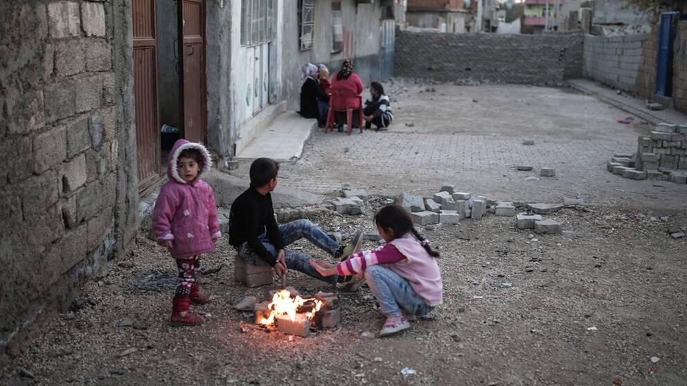 Barn leker på en gata i Cizre, där PKK-gerillan byggt upp barrikader.