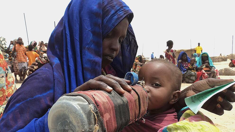 En kvinna ger sitt undernärda barn vatten ur en flaska.
