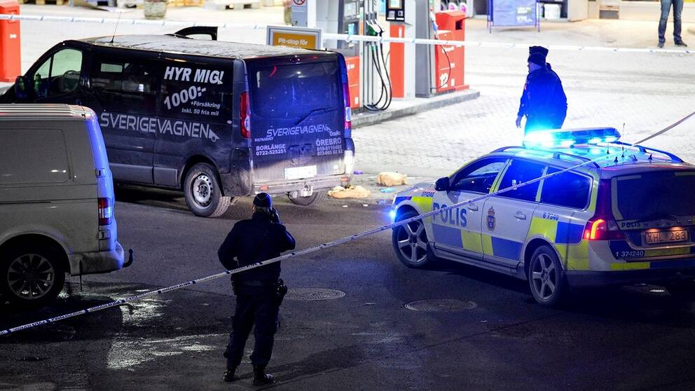 Polisbilar vid den plats där mannan i Fittja sköts under lördagseftermiddagen.
