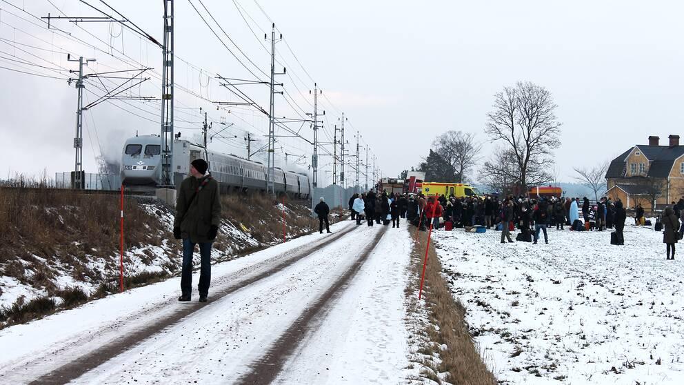 Evakuerade människor på ett gärde i snön. Tåg som ryker. Ambulans och räddningstjänst.
