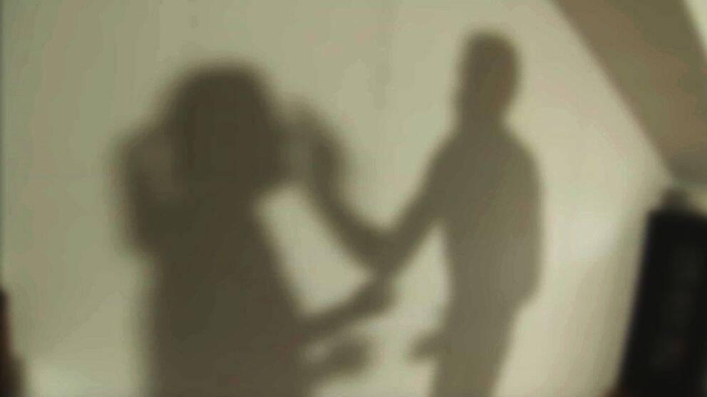 En anonym skuggbild med en man som slår en kvinna.