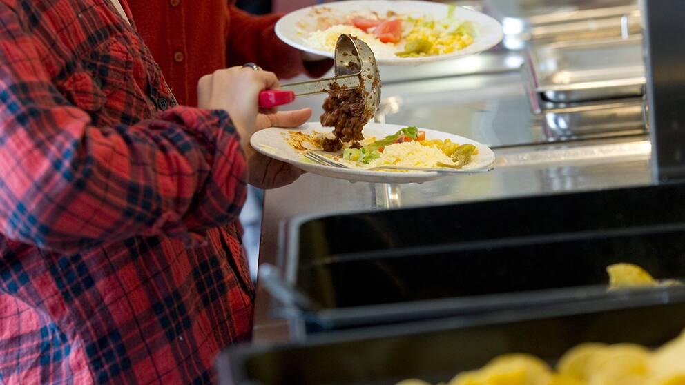 Barn lägger upp mat i en skolmatsal.