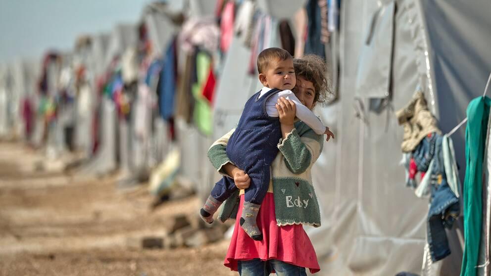 En syrisk flicka bär en baby i ett flyktingläger i Turkiet.