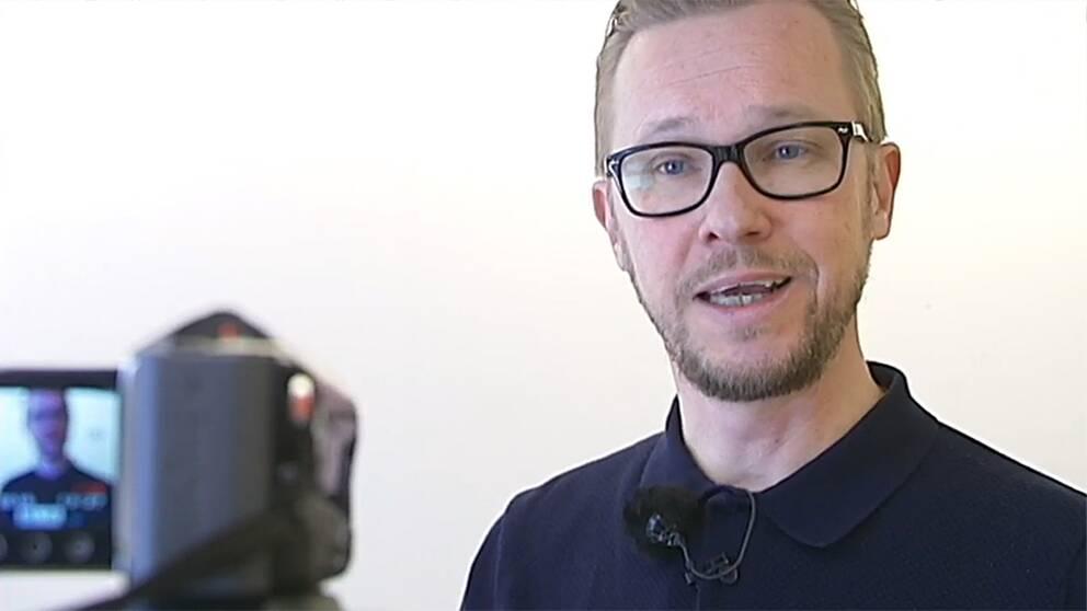 Micke Sandström framför en videokamera.