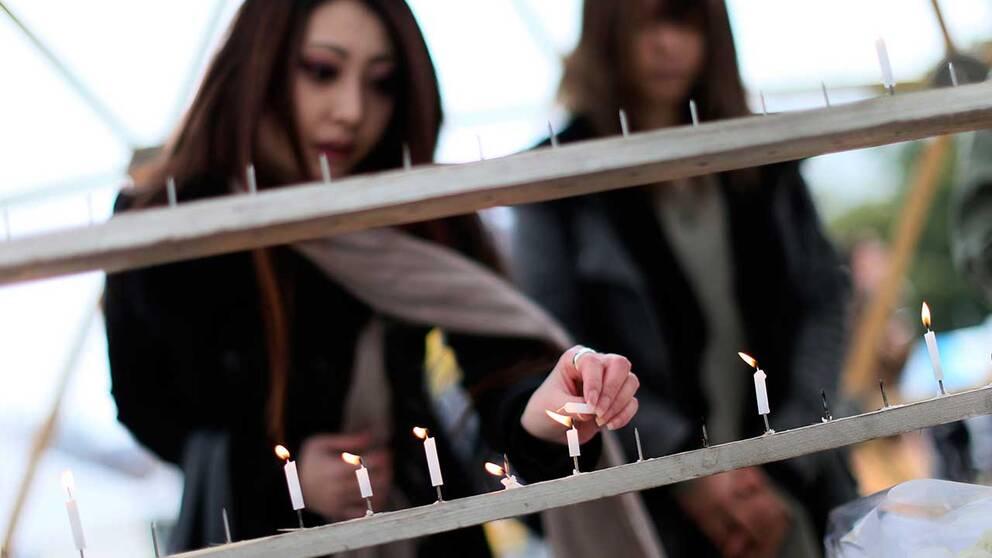 Ung kvinna tänder ljus för offren på femårsdagen av Fukushima-katastrofen.
