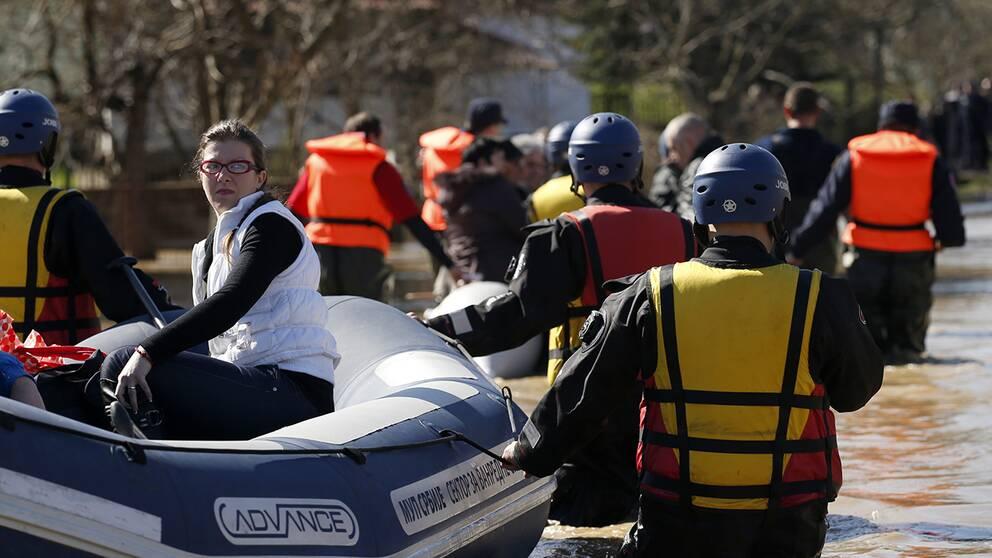 Serbisk polis evakuerar invånare från ett översvämmat område i byn Grdica.
