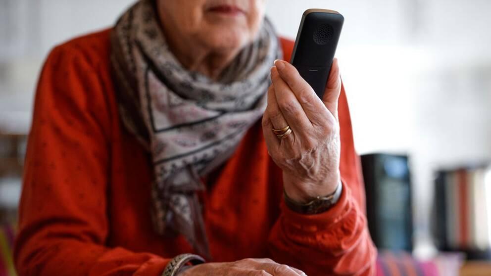 En äldre person med en telefon i handen.