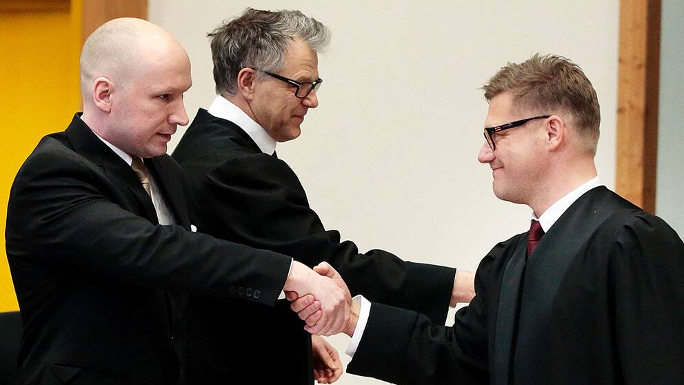 Breivik hälsar på regeringsadvokaten Marius Emberland. Emberland företräder norska staten som Brevik stämt.