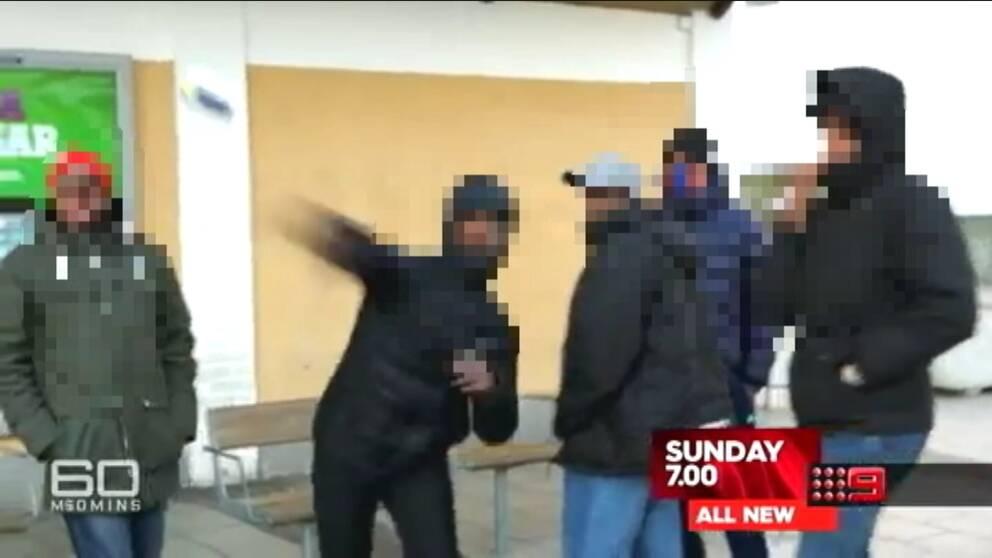 Maskerad person kastar en burk mot kameran.