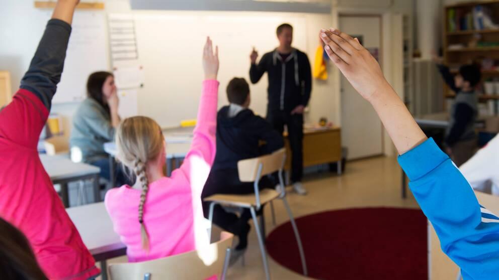 Barn som räcker upp handen i klassrum.