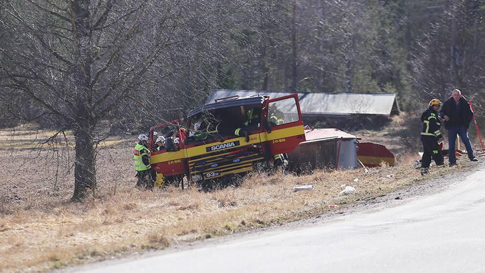 Brandbil i diket, räddningspersonal runt omkring.