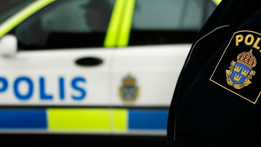 Polisbil och axel på polis med polislogga.