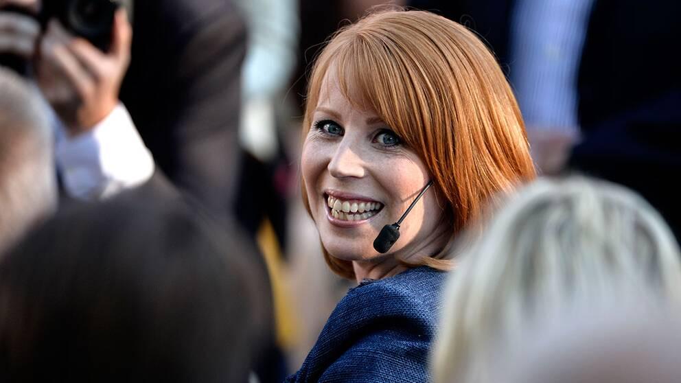 Annie Lööf som ler i en bland människor runtomkring.