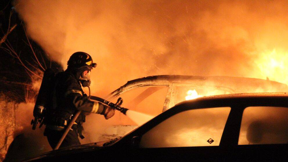Brandman släcker bilbrand.