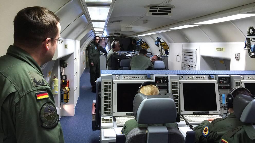 Män arbetar i stridsutrymmet i ett AWAC-flygplan.