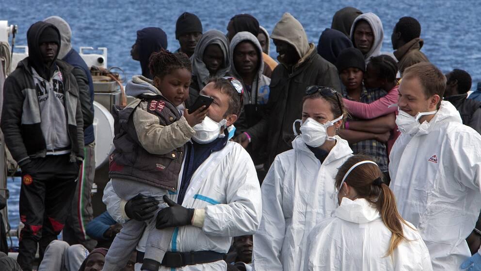 Italienska kustbevakningen tar hand om människor i Sicilien i mars 2016.