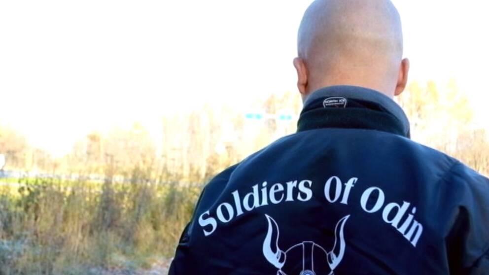 Ryggen på en man med rakat huvud som bär en jacka med texten Soldiers of Odin.