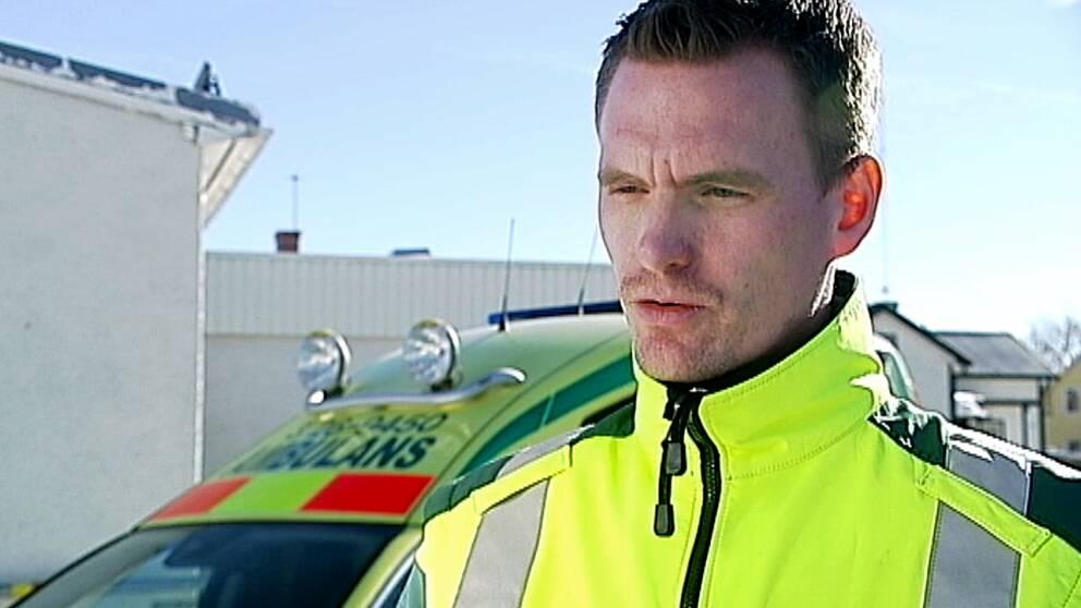 man i reflexjacka framför ambulans