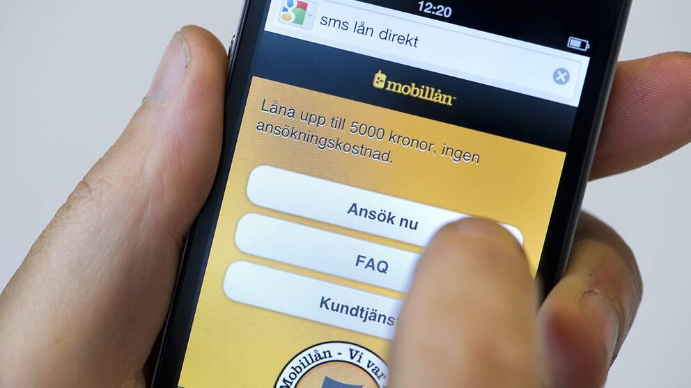 En person håller på att ta ett sms-lån med hjälp av sin mobiltelefon.