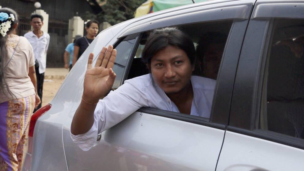 En av de frigivna samvetsfångarna, Tin Htut Paing, vinkar när han lämnar fängelset.