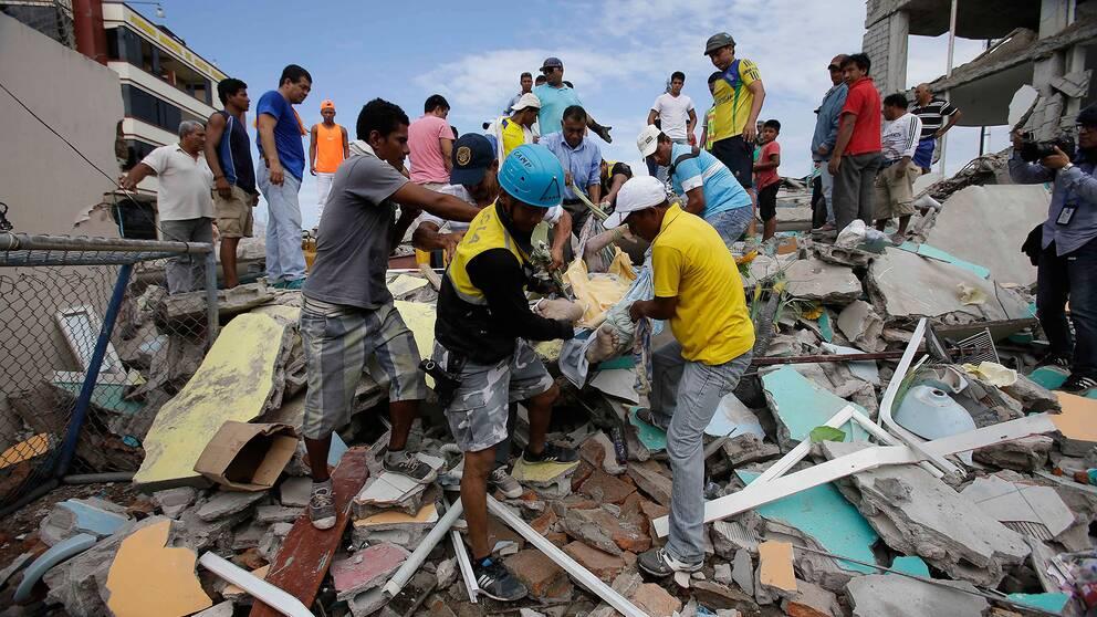 En skadad man dras fram från ett raserat hus i Ecuador
