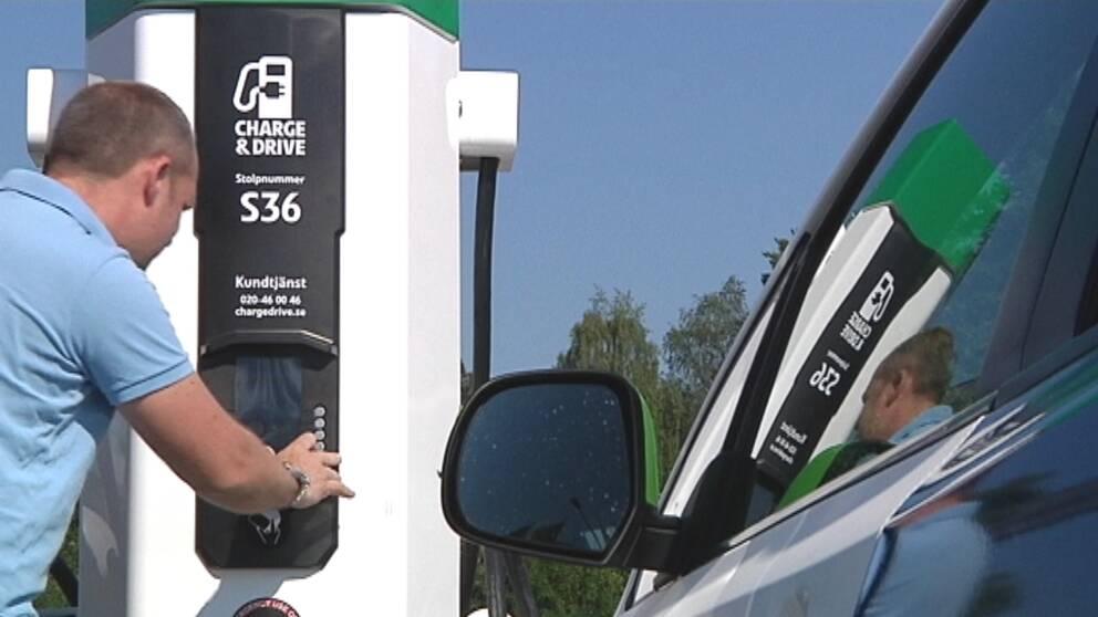 En bil står intill en laddstation. En man trycker på en av knapparna på laddstationen.