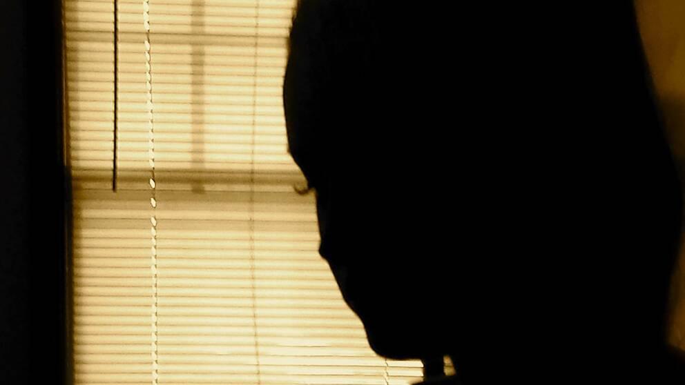 Ung kvinna står vid ett fönster med neddragna persienner. Hela arvet som hennes pappa lämnat efter sig har försvunnit.
