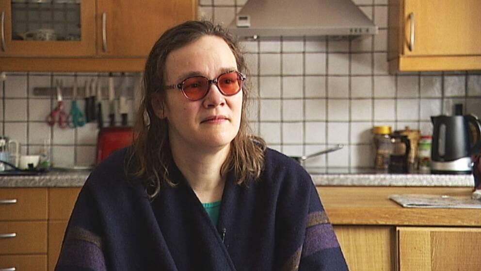 En kvinna med mörkt hår med röda solbrillor på i sitt kök.