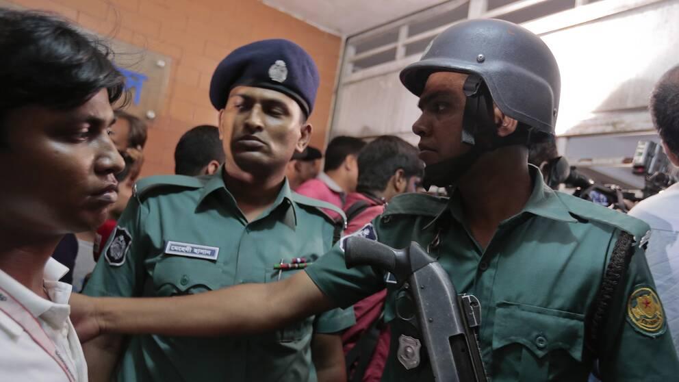 Bangladeshisk polis utanför lägenheten i Dhaka där två män mördats.