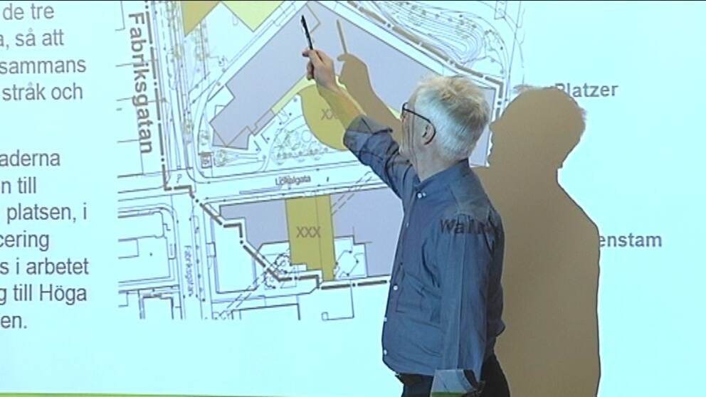 En man står framför en karta av området och pekar ut var husen ska byggas.