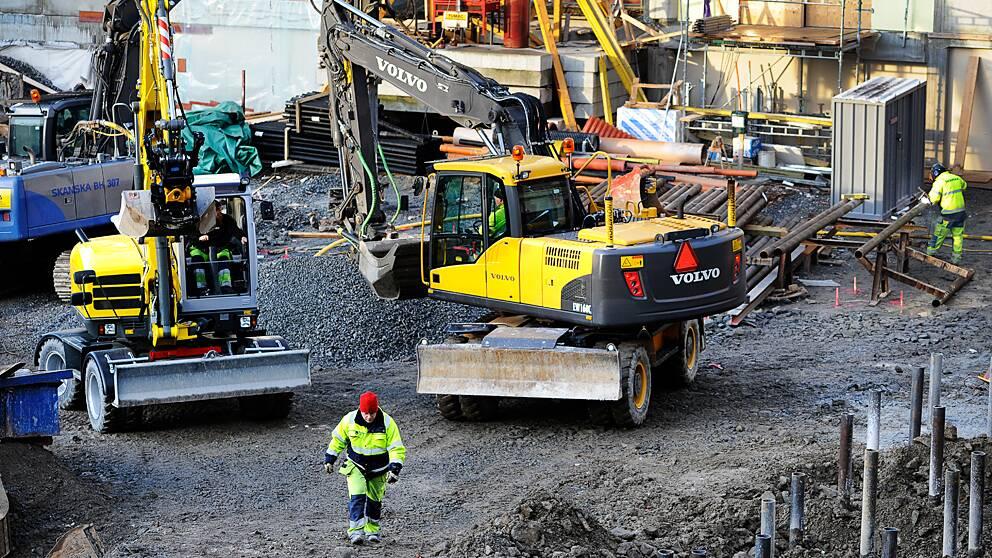 En byggnadsarbetare och olika maskiner på en byggarbetsplats