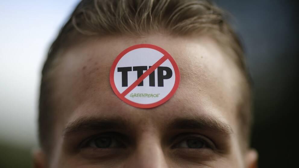 Greenpeaceaktivist med ett anti-TTIP-märke i pannan.