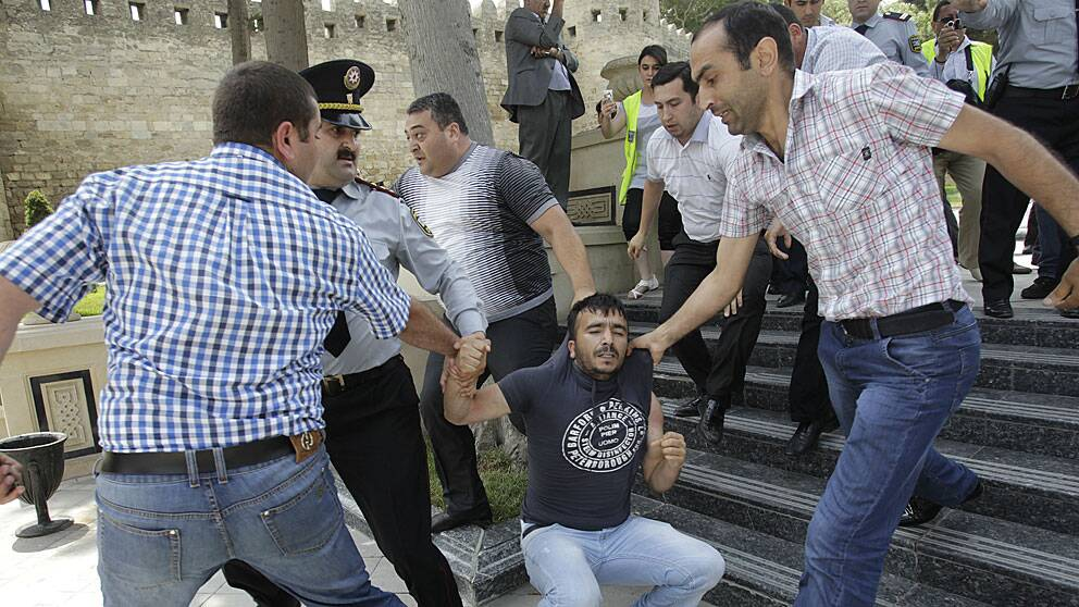 En demonstrant grips av civilkllädda azerisk poliser