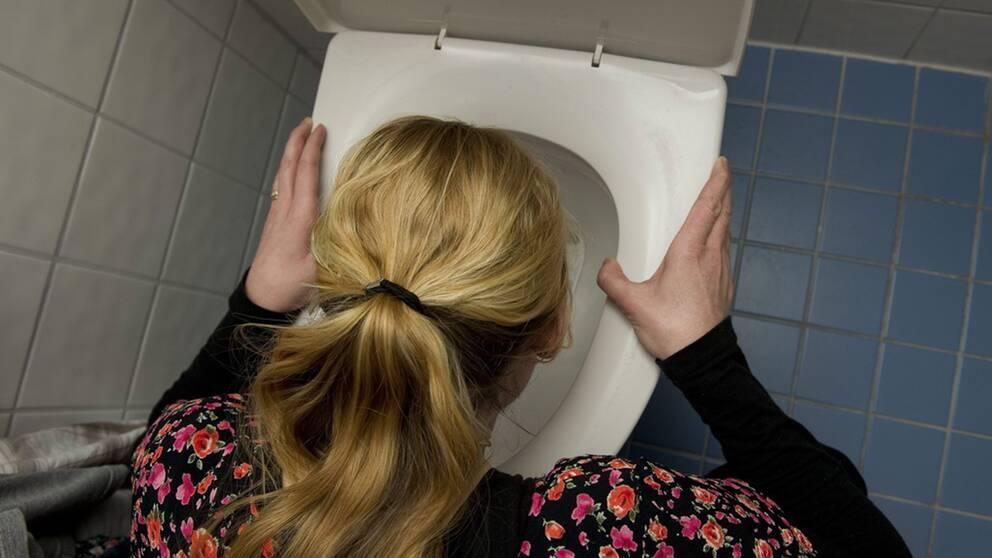 Kvinna hukar över toalett.
