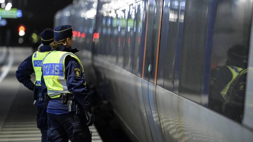 Poliser som står bredvid ett Öresundståg.