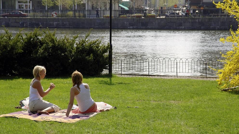 Två kvinnor sitter på en gräsmatta vid vatten.