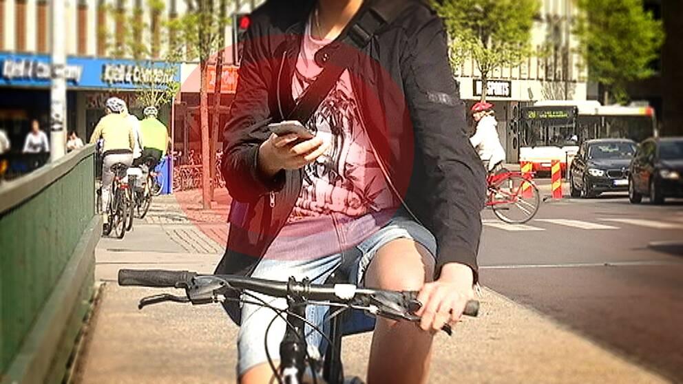 Cyklist tittar på mobilen medan han cyklar.
