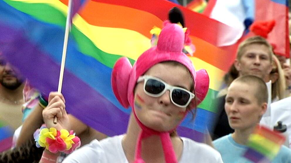 En bild på en person som går med i ett Pride-tåg.