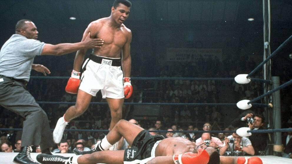 Mohammad Ali hålls tillbaka av domaren Joe Walcott efter att han knockat motståndaren Sonny Liston i första ronden under en match i Lewiston, Maine 1965.