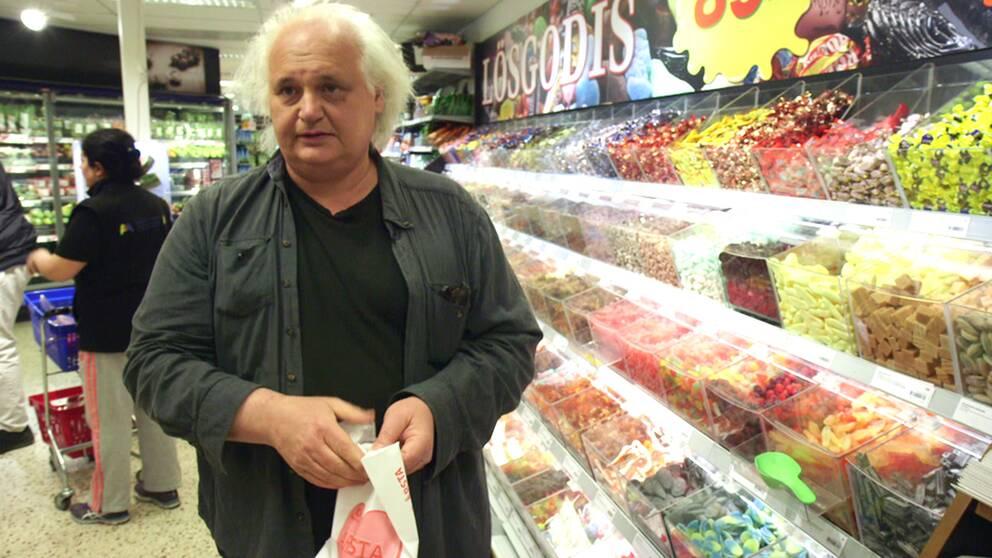 Göran Greider framför en avdelning med lösviktsgodis.