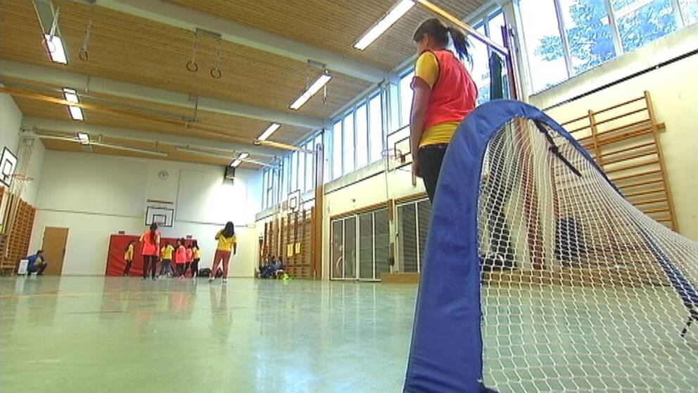Skolidrottshall med barn som spelar innefotboll.