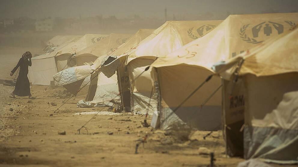 En kvinna går genom flyktinglägret Zaatari, i Jordanien. Väderförhållandena i lägret är svåra, med omväxlande kyla och hetta samt sandstormar.