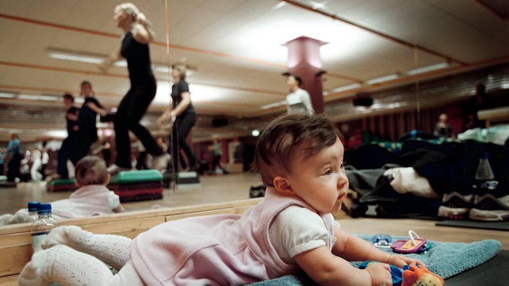 Barn ligger på en matta i en träningssal.