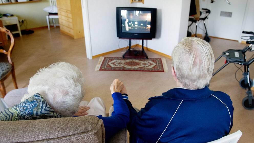 Ett äldre par håller varandra i handen och tittar på tv i sin lägenhet.