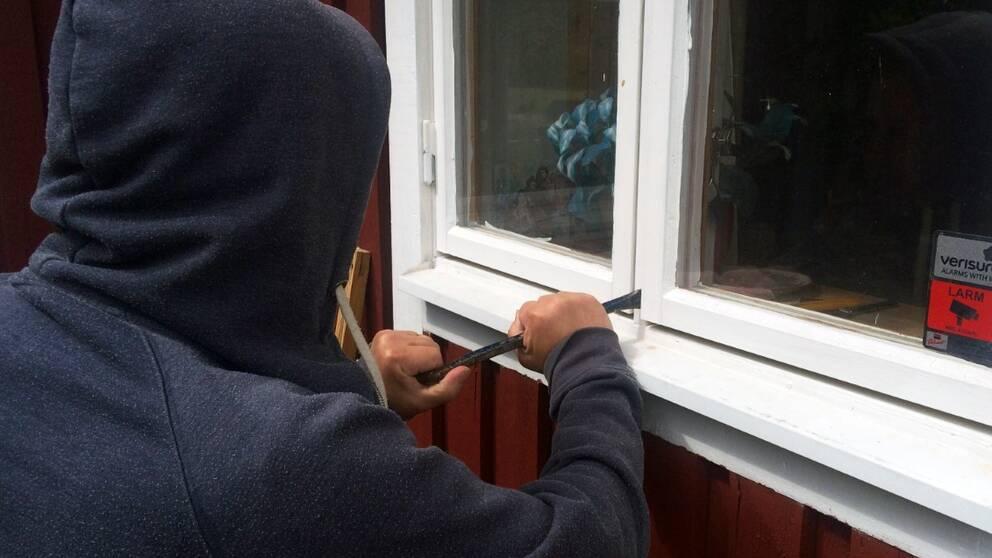 Anonym inbrottstjuv med huvtröja som har en kofot vid ett villafönster