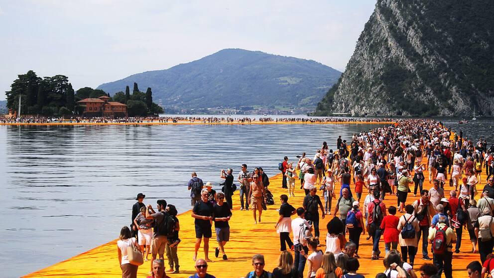 """Konstverket """"The Floating Piers"""" av Christo, där besökarna får uppleva det som att gå på vatten."""