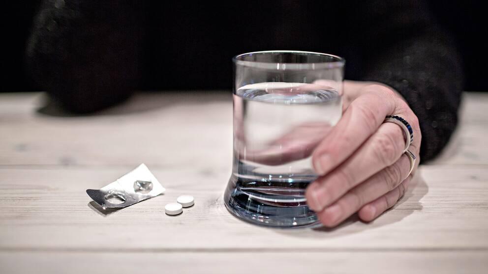 Smärtstillande tabletter och ett vattenglas