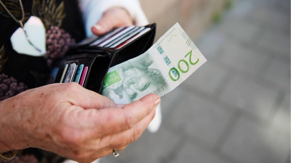 Kvinna som tar fram en sedel ur sin plånbok.