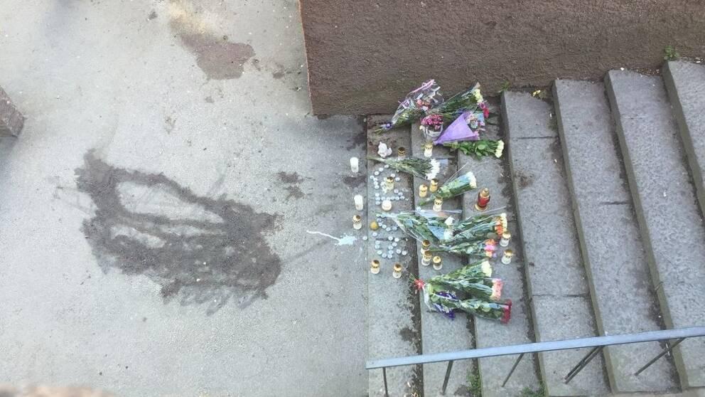 Blommor och ljus vid brottsplatsen i Tensta.